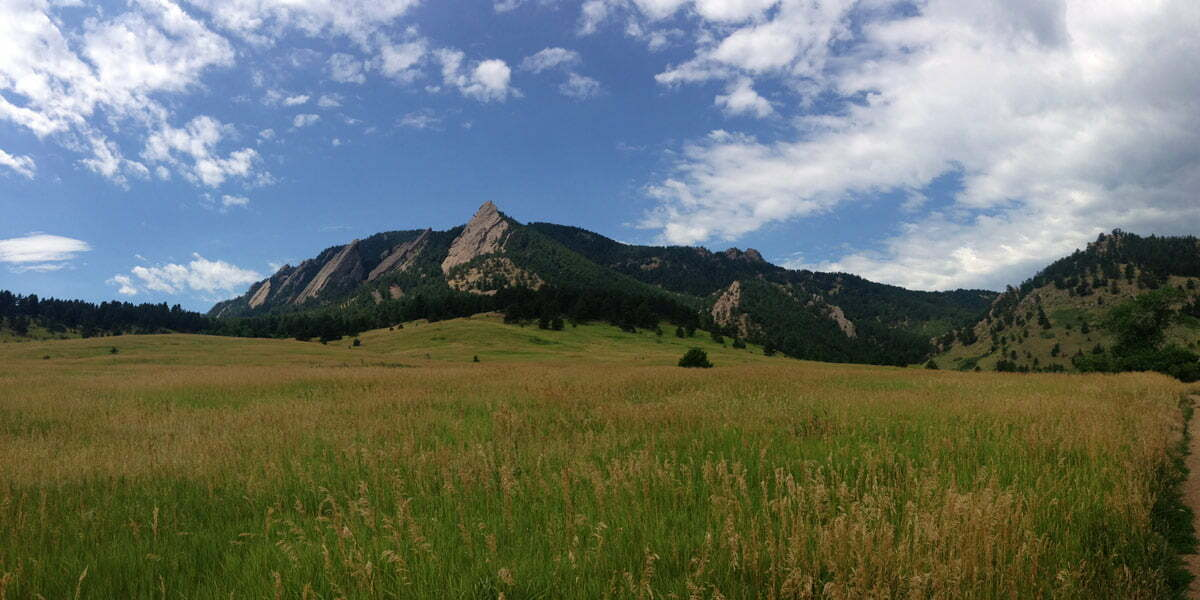 A panoramic photo of the yellow and green fields before the hike up Flagstaff Mountain in Boulder, Colorado.