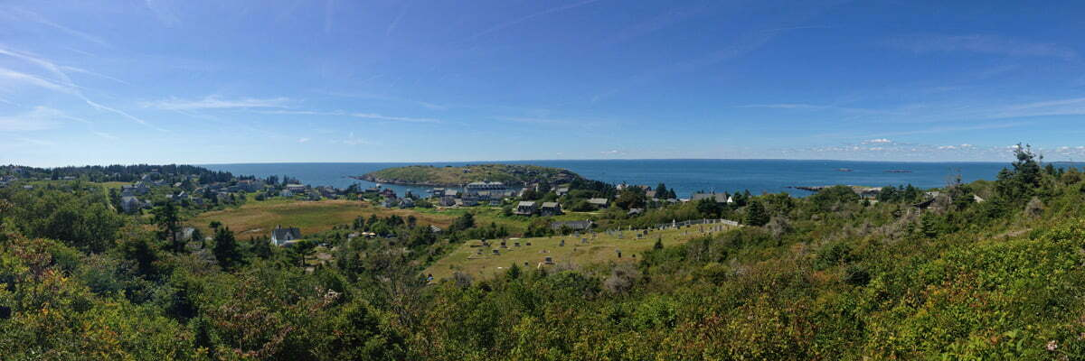 A panoramic photo of a blue sky and green landscape of the small rocky island of Monhegan off the coast of Maine.