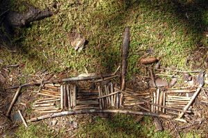 An arrangement of sticks to form a boat in some forest moss on Monhegan Island in Maine.