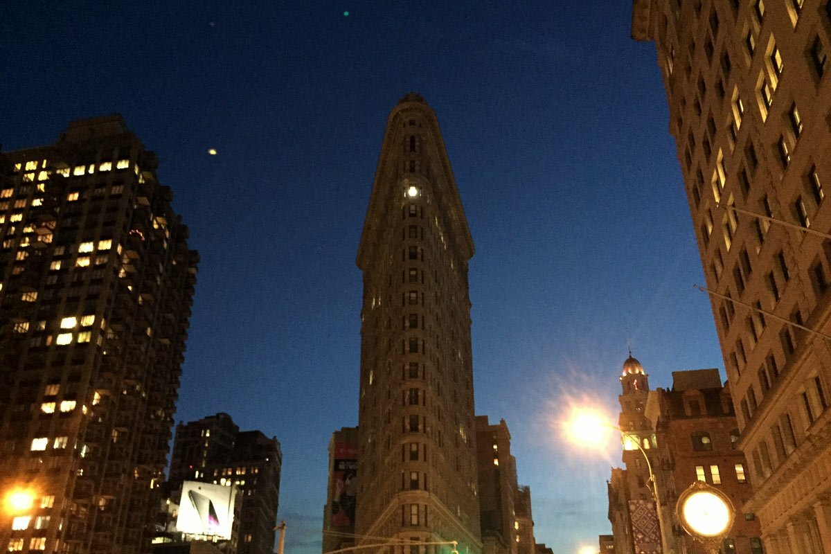 The iconic Flatiron Building in New York City seen as night falls.