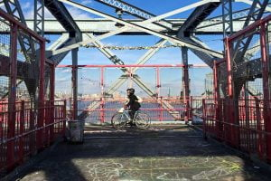 Two bikers cross the Williamsburg Bridge in New York City.