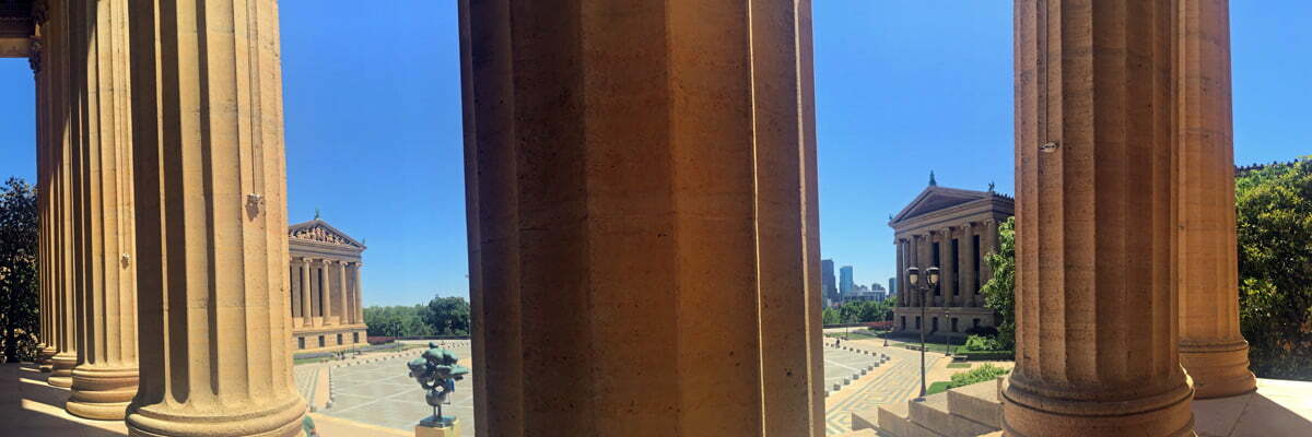 A panoramic photo taken from the steps at the east entrance to the Philadelphia Museum of Art. A series of columns break up the image with views of the open plaza and Greek buildings.