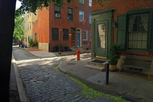 An empty, quiet side street with a cobblestone road in a tree-covered neighborhood of Philadelphia.