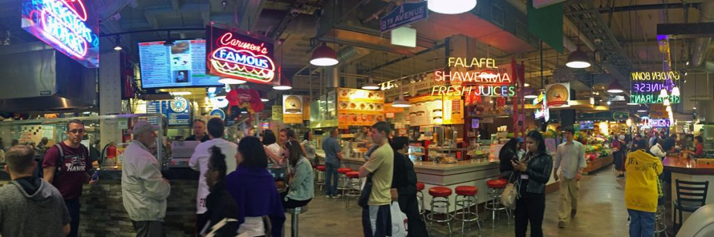 A panoramic photo of the Reading Terminal Market with a busy crowd and neon signs in Philadelphia, Pennsylvannia.