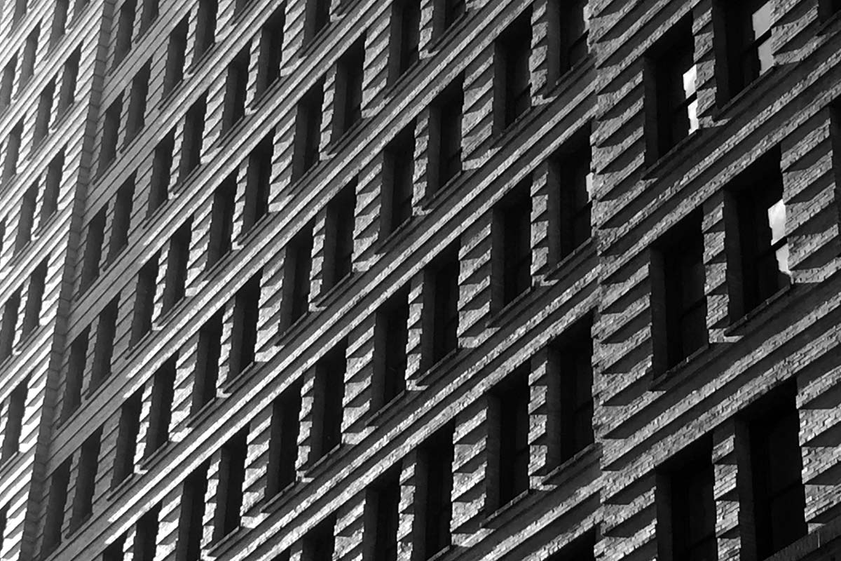 A black and white architectural image of the facade of a brick building. Photograph taken in the late afternoon light with shadows being cast across the structure in downtown Philadelphia, Pennsylvania.