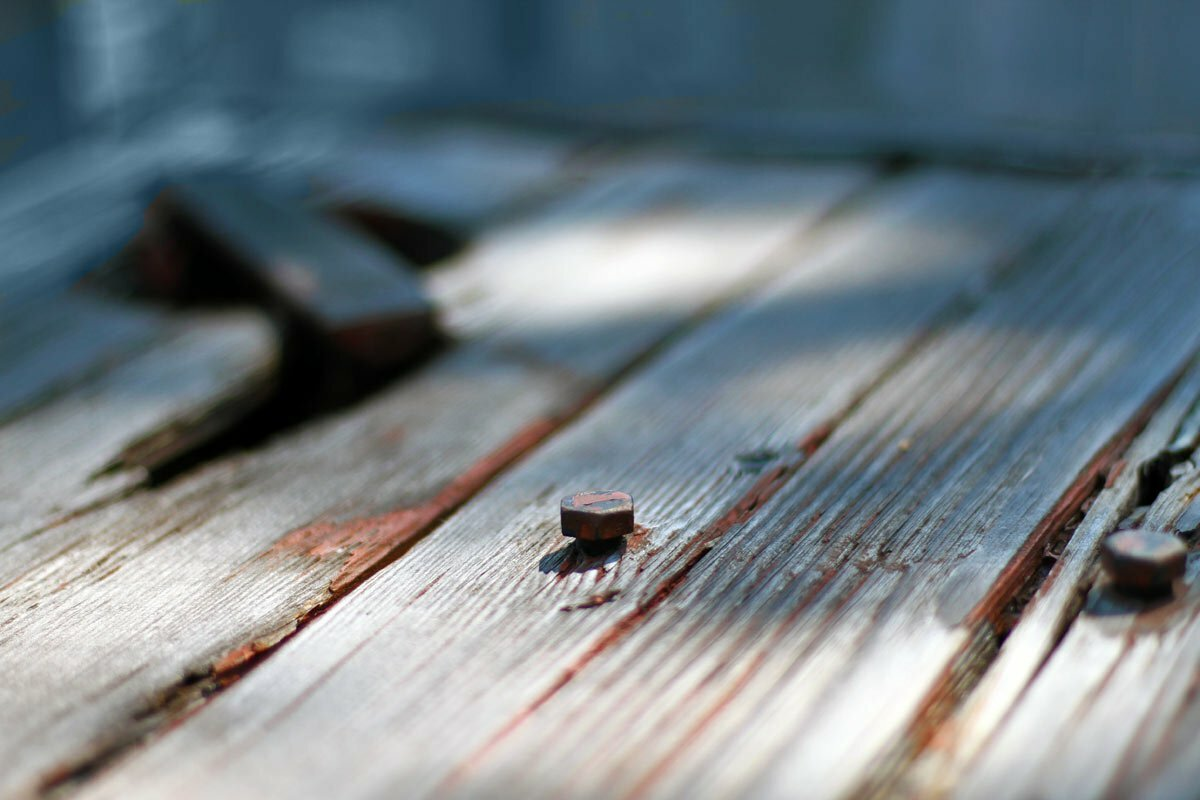 A hex screw in a weather worn, old wood table.