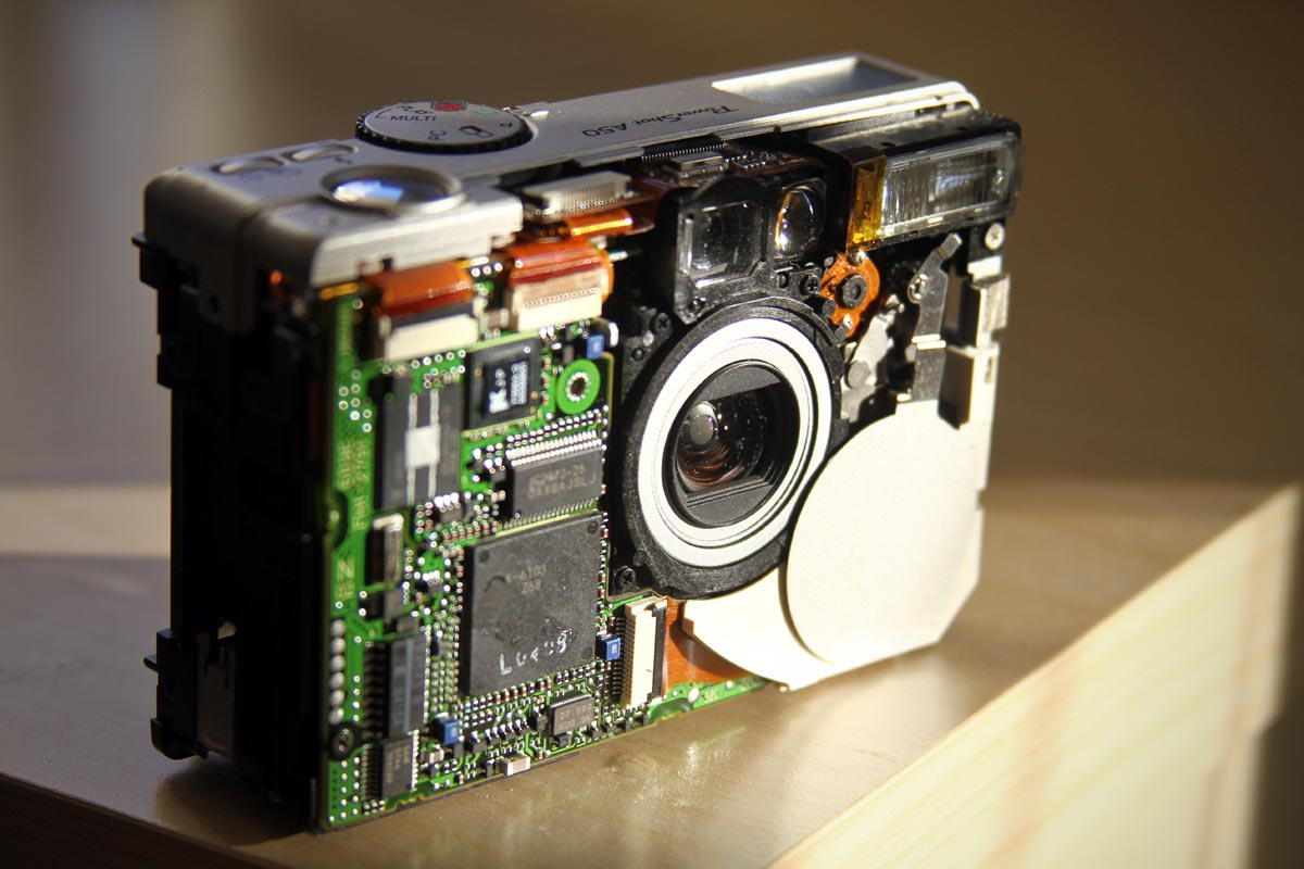 An old Canon PowerShot A50 being taken apart after the faceplate was removed with the computer chip, lens and other internal components visible.