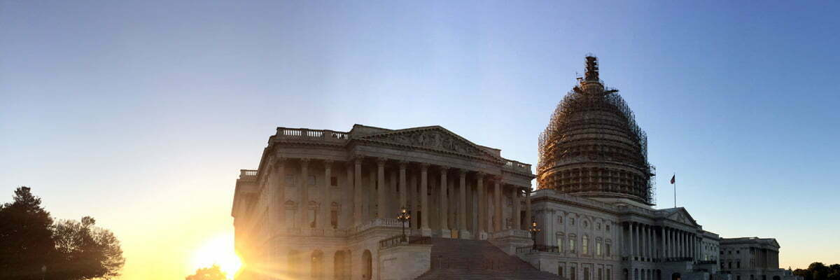 The East side of the United States Capitol with the sun setting in the lower left corner.