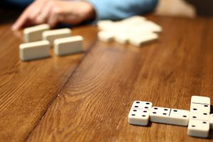 A game of dominoes takes place on a wood table.