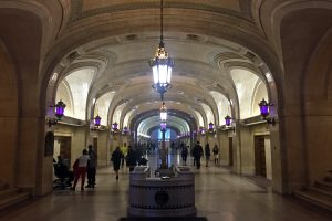 The ornate hallways of the lobby in the Chicago City Hall building with purple lights.