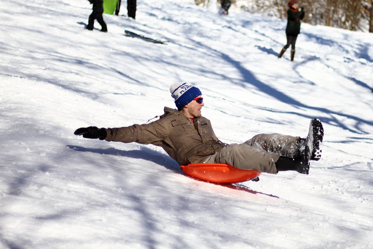 An adult on a plastic saucer sled reaches for balance going downhill in Washington DC during Winter Storm Jonas, also known as Snowzilla.