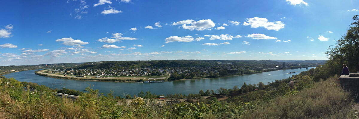A panoramic photo taken on a cloudy day with blue skys over the Ohio River looking towards Kentucky from Cincinnati.