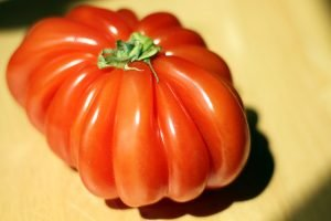 An unusually shaped red heirloom tomato with fluted shoulders.