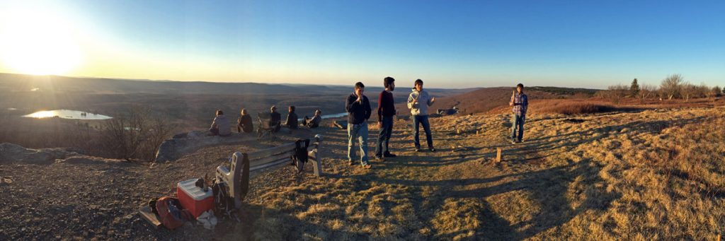 A group of friends hang out on a mountaintop to watch the sun setting in Canaan Valley, West Virginia.