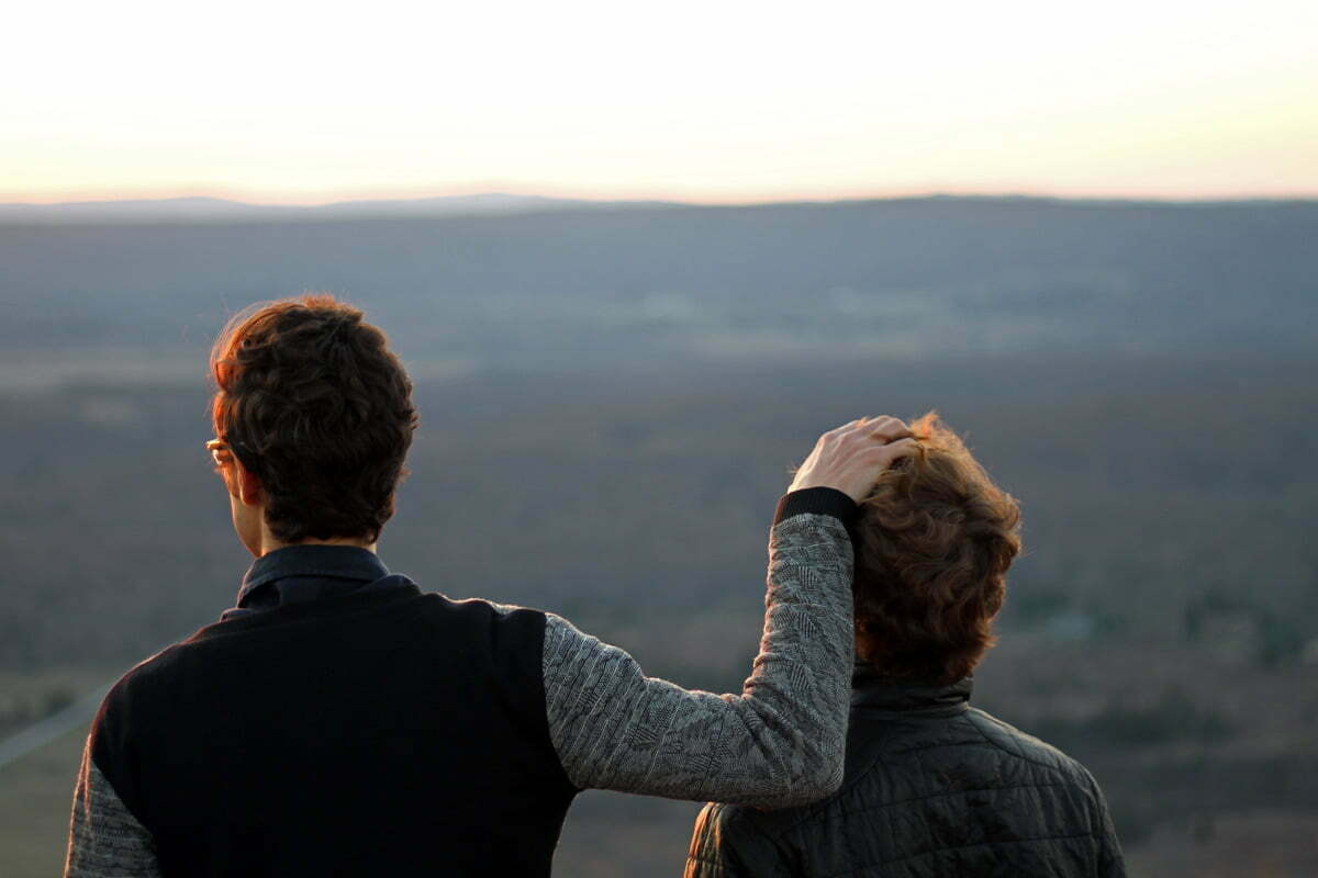 Two friends stand to watch the sun setting over a mountain with one running his hands through the hair of his friend.