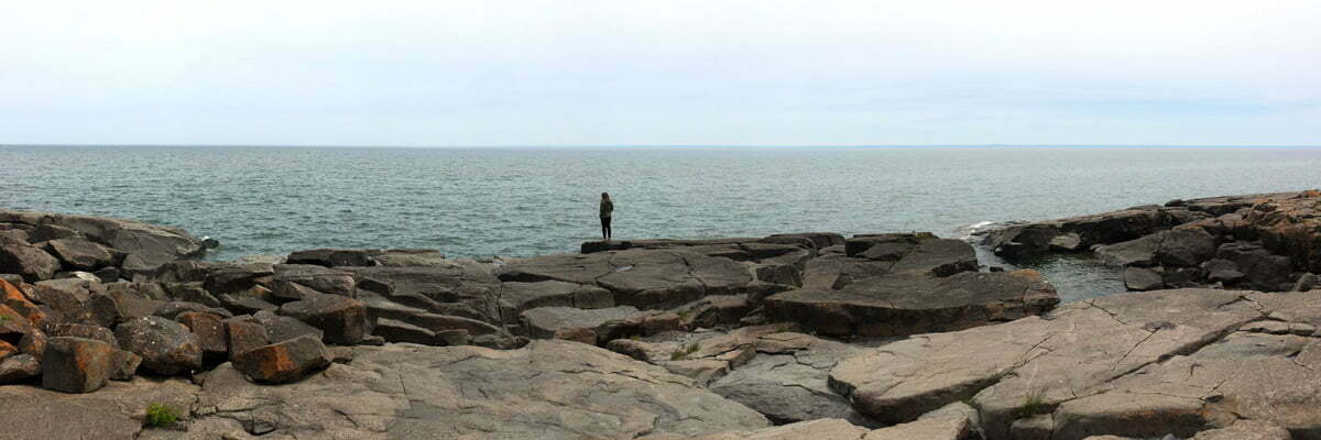 A panoramic photo of a woman standing and looking out from Stony Point outside Duluth, Minnesota on Lake Superior.