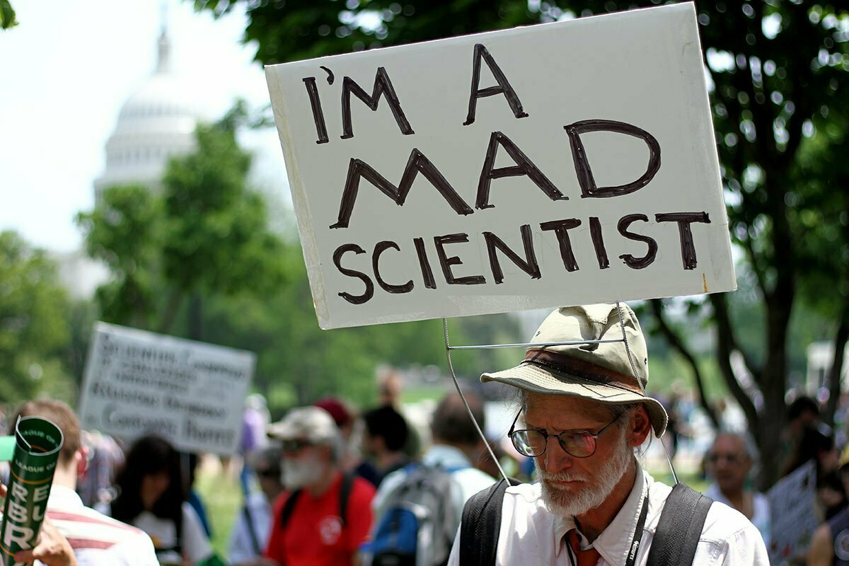 """A man with a sign saying """"I'm a mad scientist"""" at the People's Climate March in Washington DC with the US Capitol building in the background."""