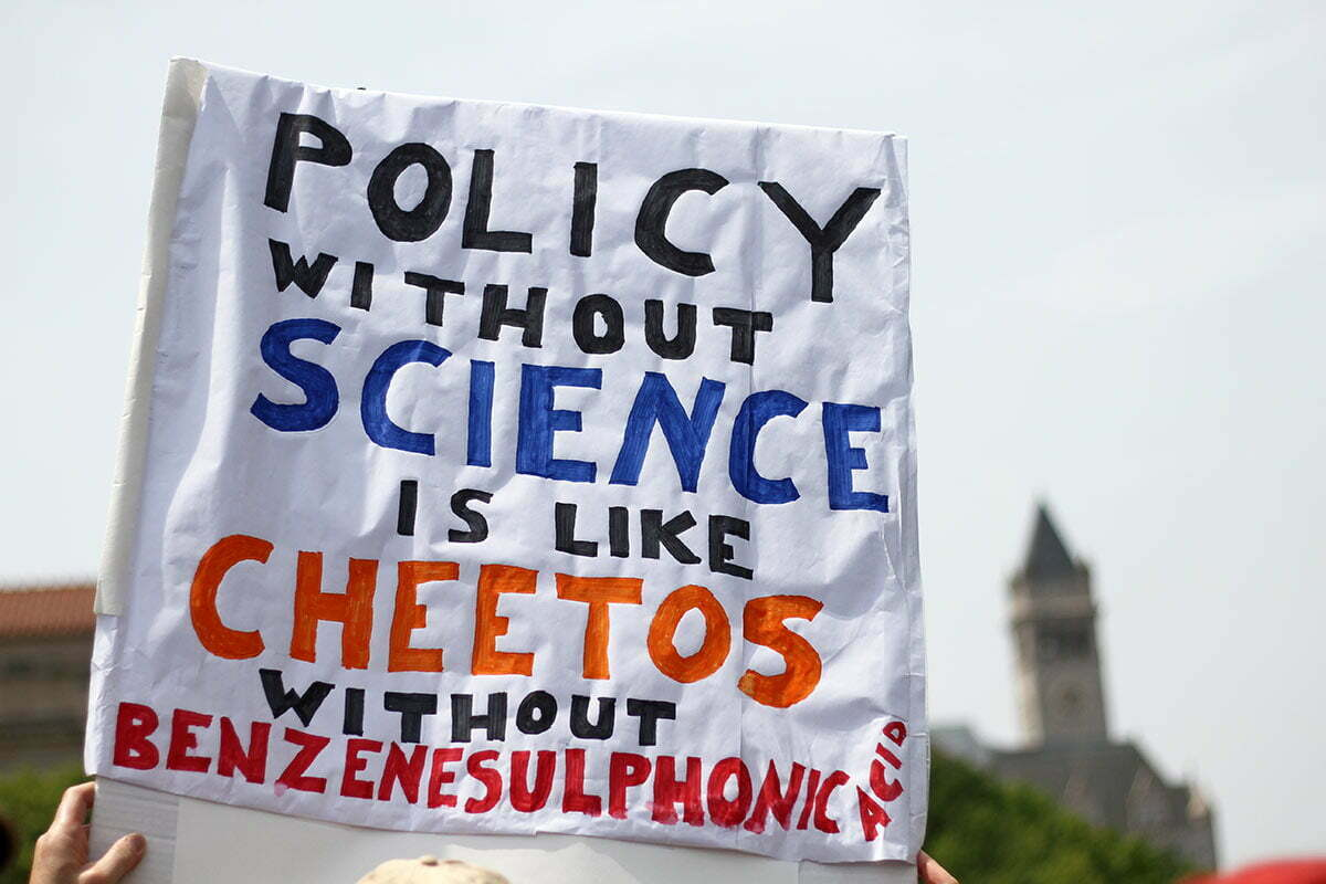 """A protester at the People's Climate March near the Trump Hotel holding a sign saying """"Policy without science is like cheetos without benzenesulfonic acid."""""""