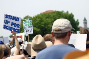 """A protester at the People's Climate March in Washington DC holds a sign saying """"Stand up for Science."""""""