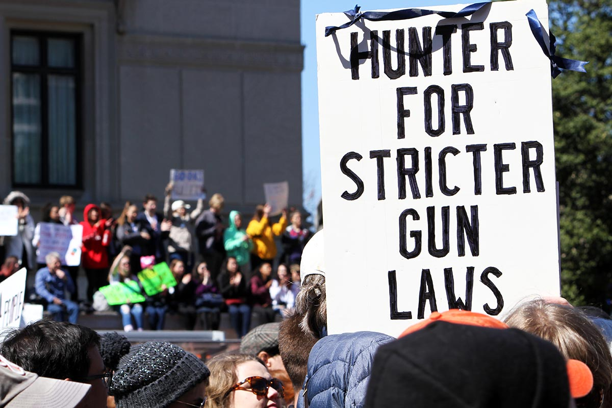 A man holds up a sign that says 'Hunter for Stricter Gun Laws' at the March for Our Lives in Washington DC.