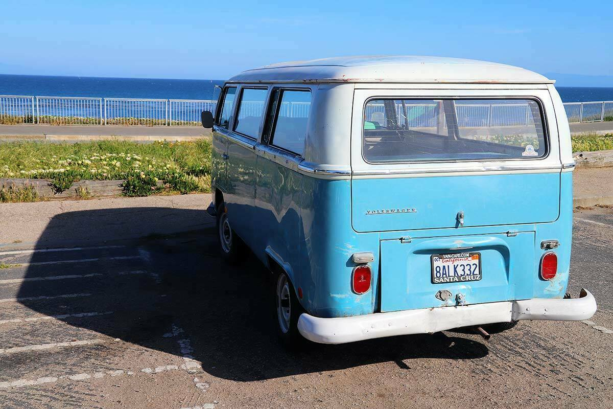 A blue Volkswagen bus parked on the cliffs of Santa Cruz, California overlooking the Pacific Ocean.