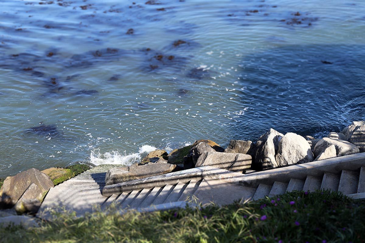 Waves crash into the stone steps used by surfers that goes down to the ocean in Santa Cruz, California.