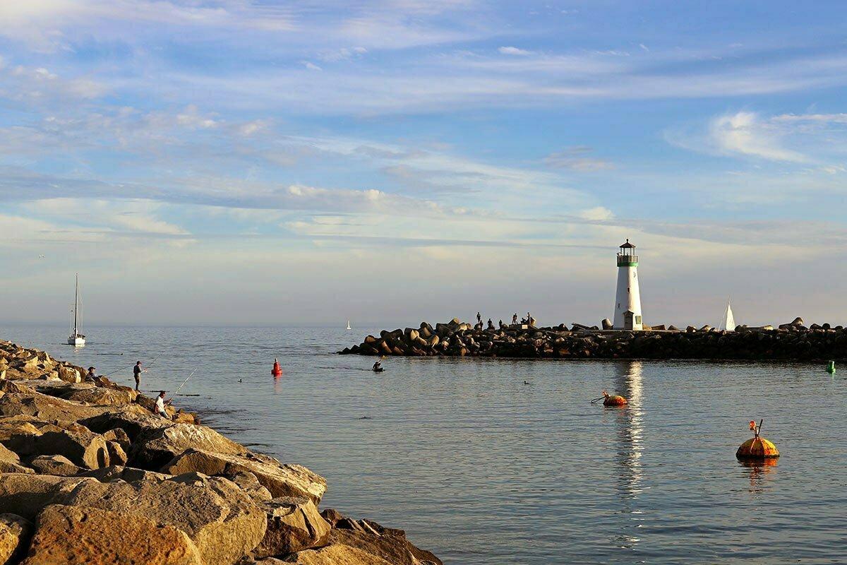 An active sunset scene of people fishing, sailing, kayaking and playing near the Santa Cruz Breakwater Light, also known as the Walton Lighthouse in Santa Cruz, California.