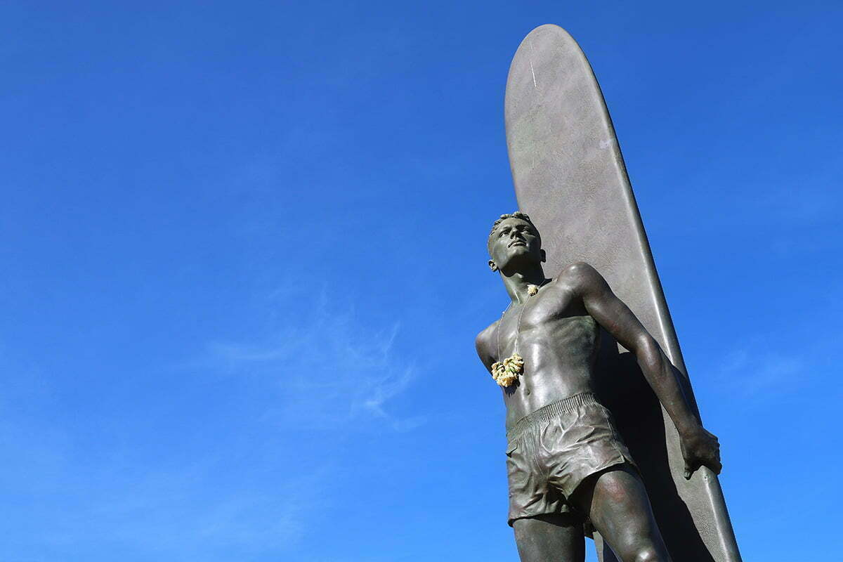 A bronze statue in Santa Cruz, California of a surfer with a lei of flowers around his neck.