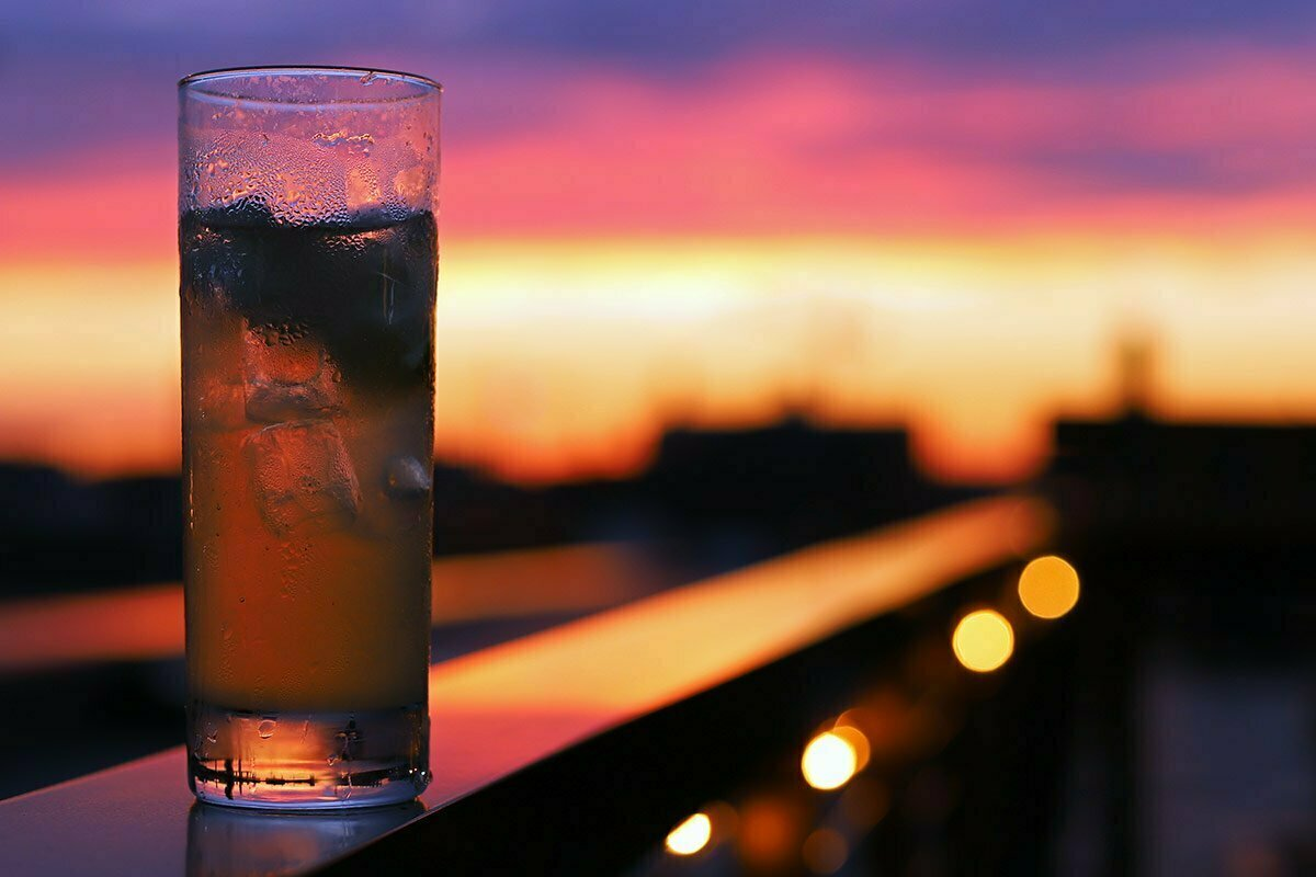 A photograph of a tall glass of gin and tonic with ice cubes sits on a ledge with a spectacular sunset in the background.