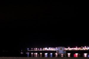 The Santa Cruz Wharf seen in the dark from the beach on a summer night in California.