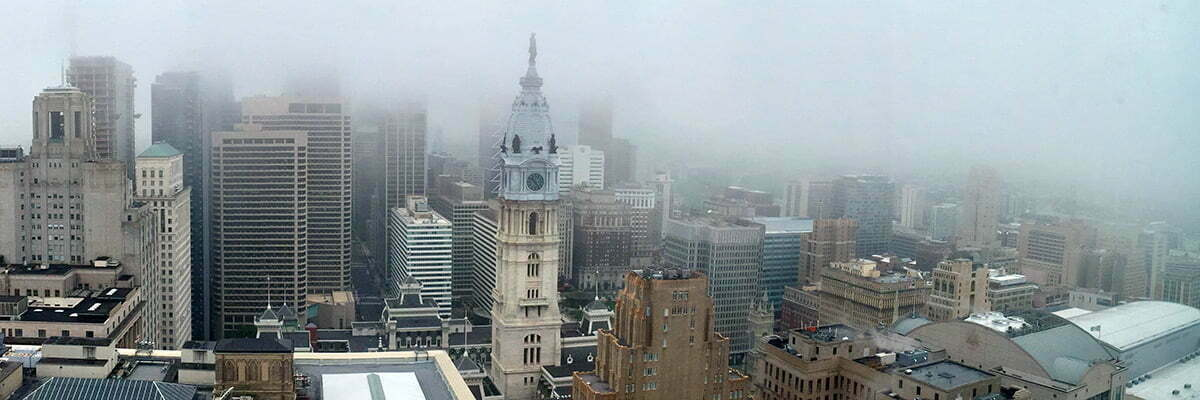 A view of the skyline of Philadelphia and city hall on a very cloudy day.