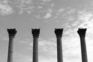 A black and white photograph of four classical columns and a cloudy sky seen at the National Arboretum.