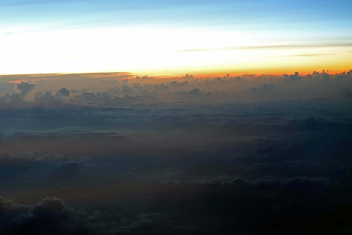 An orange sunset breaks over the clouds as seen from a plane over the Caribbean Sea.