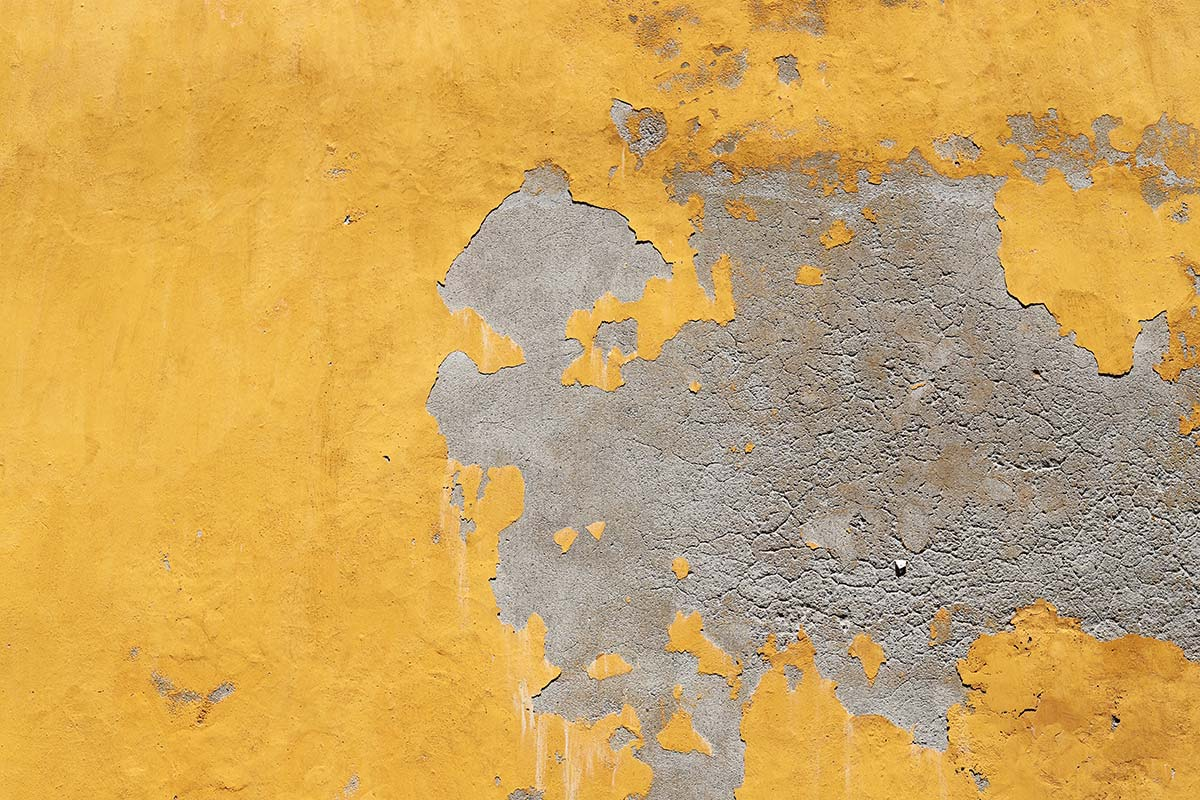 A concrete wall with bright yellow paint peels and cracks in Cartagena, Colombia.