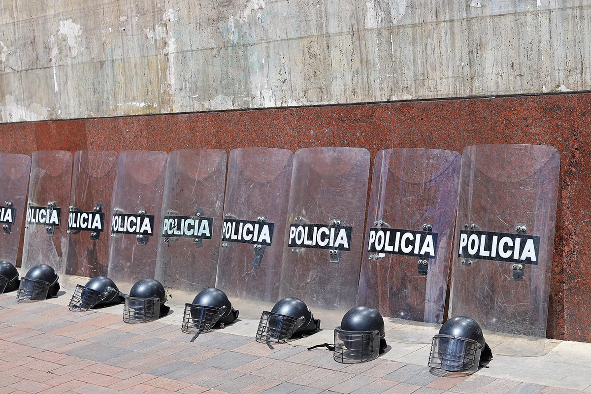 Riot police helmets and shields lay against a wall before a protest in Bogotá, Colombia.