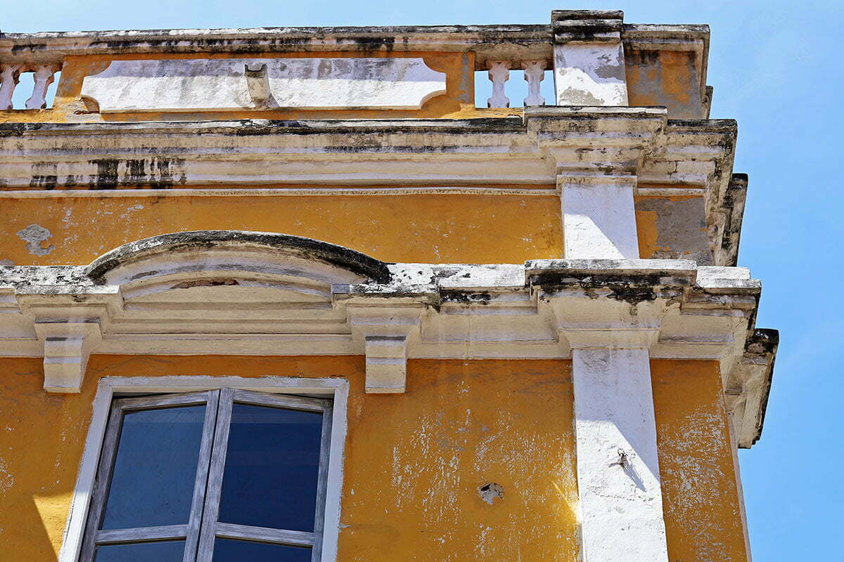 A fading yellow and white building within the colonial walled city in Cartagena, Colombia.