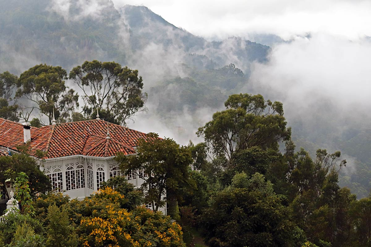 Restaurante Casa San Isidro, flowering trees and the foggy hillside is seen from Monserrate in Bogotá, Colombia.