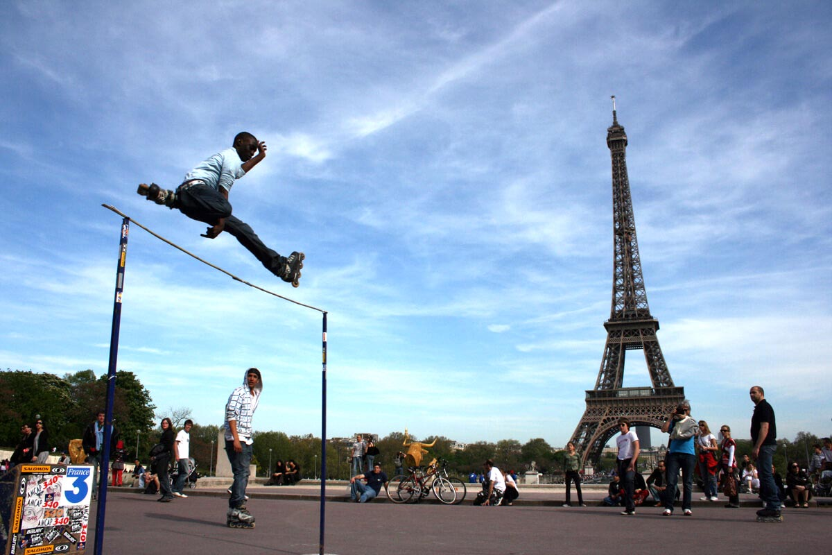 A Paris skater on rollerblades jumps over a high bar with onlookers and the Eiffel Tower in the background.