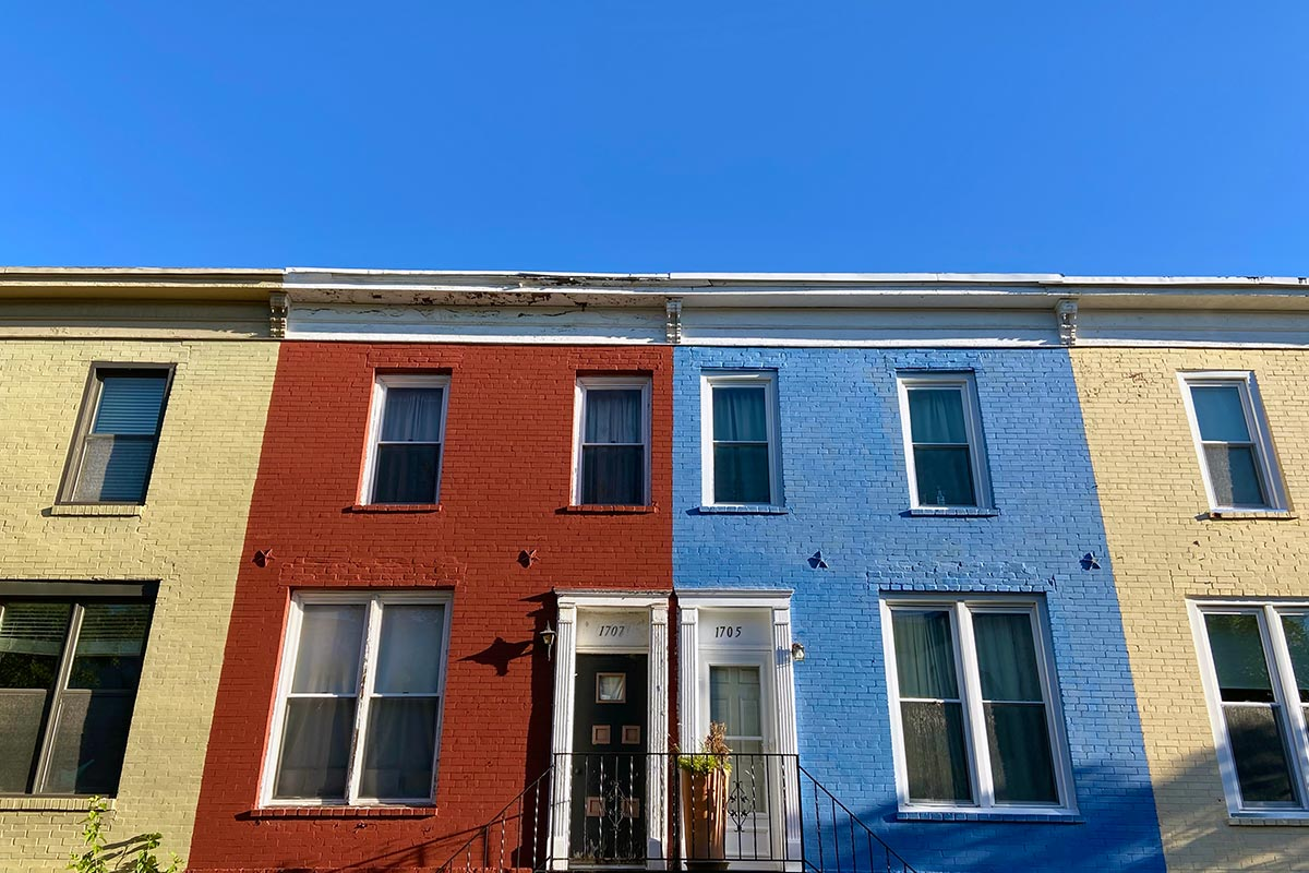 The front of a series of attached row houses in different colors seen on Seaton Street NW in Washington DC.