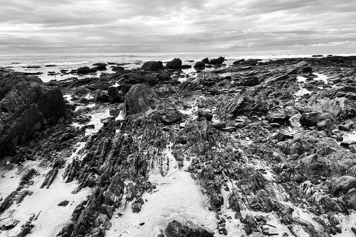 A black and white photo of a curving rock formation along the beach near Pelican Point at Crystal Cove State Park in Newport Beach, California.