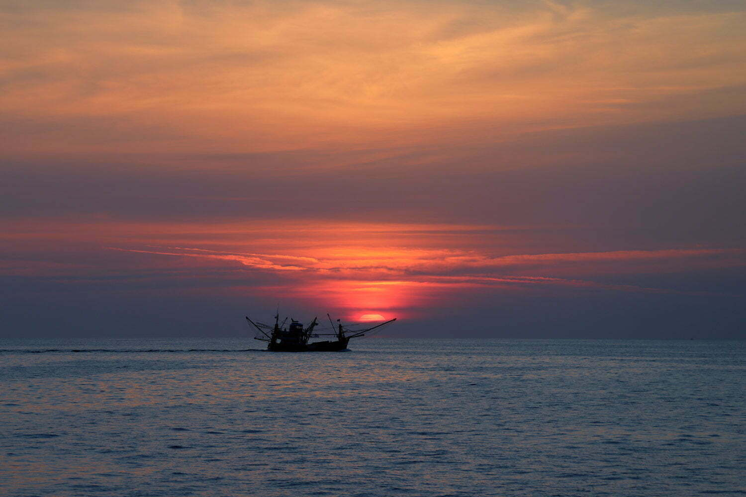 The sun sets on the ocean horizon next to a shrimper vessel rigged to start fishing off the coast of Thailand.